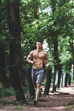 Young fit man running in the park