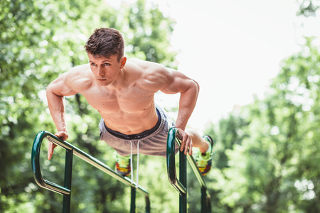 Young fit man doing push ups on bars in an outdoors gym