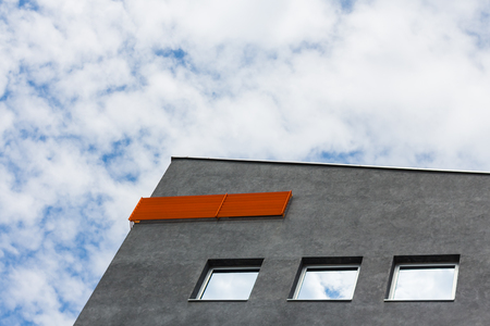 Top of gray building with orange accent and blue sky