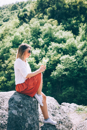 Young woman sitting on the rock in nature with flowers in her hands