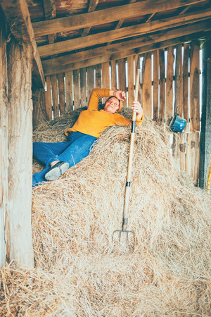 A mature woman taking a break while working on a farm, laying down in a straw Archivio Fotografico