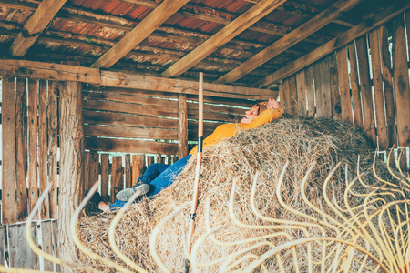 A mature woman taking a break while working on a farm, laying down in a straw 스톡 콘텐츠