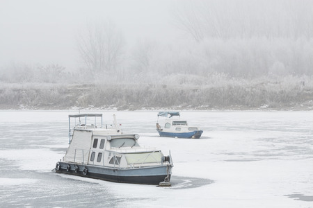 Two old boats wrecked in a frozen river Tisa near Becej, Serbia. Winter time Archivio Fotografico