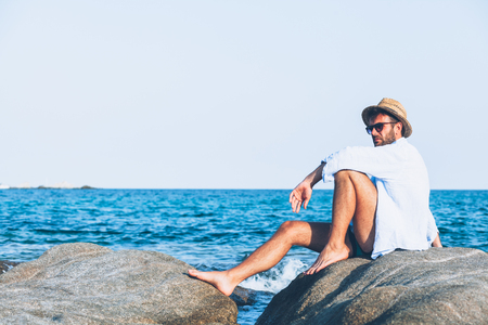 Young man relaxing on the beach, sitting on a rock near the sea