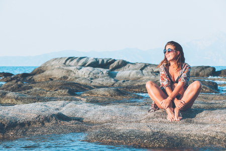 Young woman sitting on the rock enjoying sunbathing at the sea