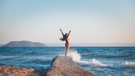 Happy young woman walking on the dock at the beach