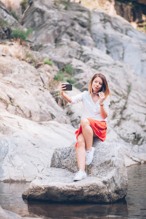 Young woman using smartphone on the lake in the springtime