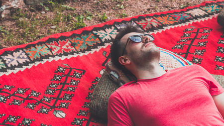 Handsome hipster lying on rug outside in the garden