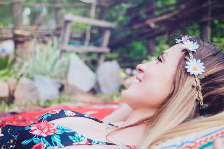 Beautiful hipster girl lying in the garden