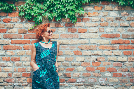 Beautiful retro older woman in front of the brick wall Zdjęcie Seryjne