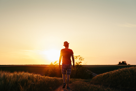Young man walking on the muddy road into the sunset