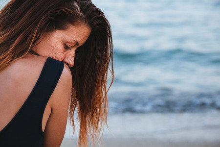 Woman alone and depressed sitting at the beach