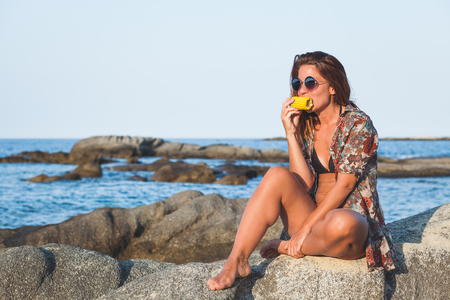 Young woman eating corn on the beach