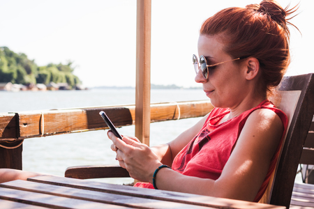 Young woman sitting in a cafe by the river using smartphone