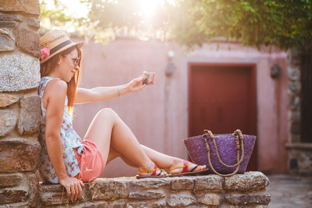 Tourist woman taking travel selfie photos with smartphone on summer holidays