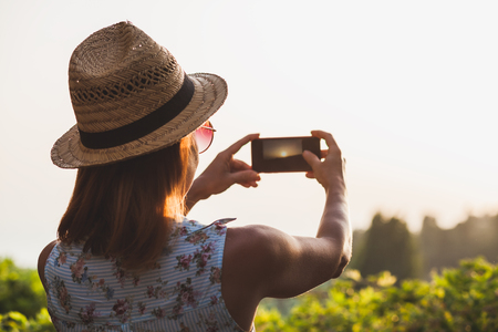 Young female tourist taking a photo of a beautiful sunset