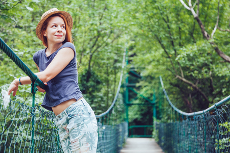Young woman in the forest on the wooden bridge enjoying summer Zdjęcie Seryjne