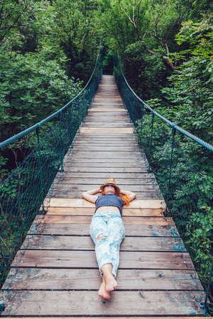 Young woman in the forest lying on the wooden bridge, enjoying summer