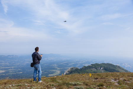 Young man flying drone over mountain
