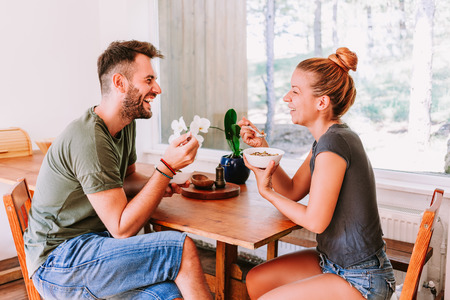 Young couple eating cereal breakfast at dining room table
