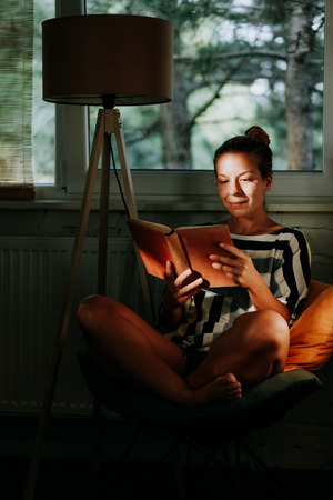 Young woman reading a book at home by the window
