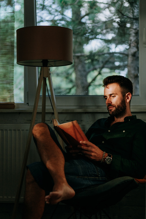 Man reading book at home by the window