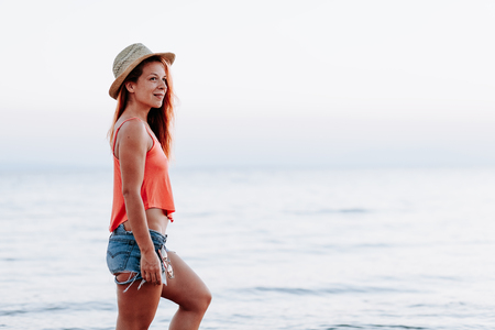 Young woman by the sea at sunset