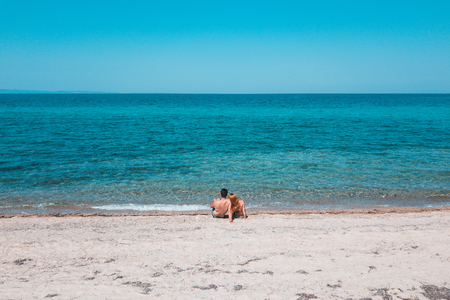 Young couple alone on the beach enjoying the view at the sea