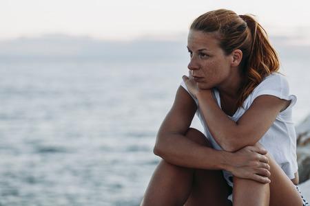 Young woman feeling sad by the sea Zdjęcie Seryjne