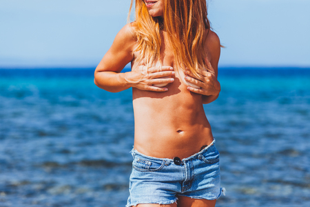 Hippie young ginger woman sunbathing topless on a beach 免版税图像