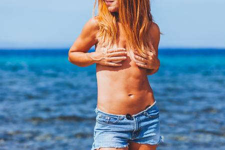 Joven hippie jengibre tomando el sol en una playa