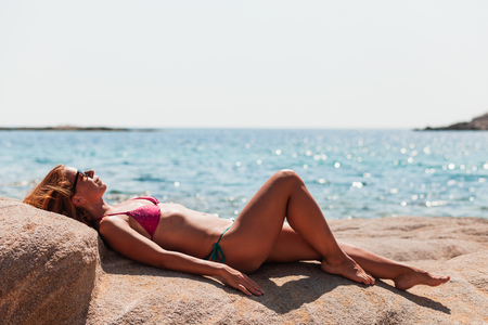 Young woman tanning on the beach Banque d'images