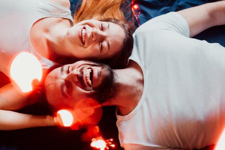 Young couple lying down with Christmas lights