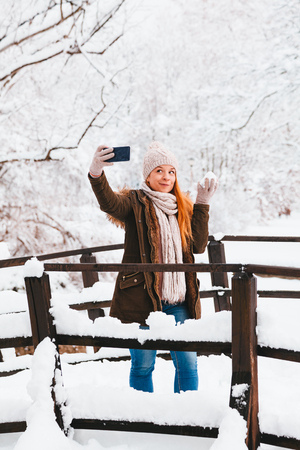 Young woman taking a selfie in a park on a snowy winter day