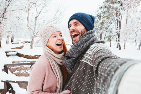 Young couple taking a selfie in a park on a snowy day