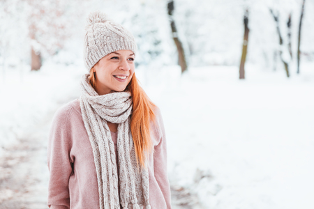 Young woman walking in the park on a snowy day