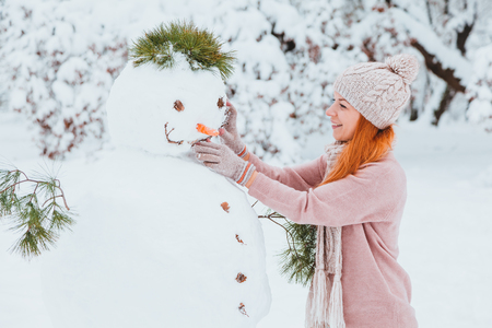Young woman making snowman in the park