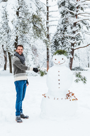 Young man making snowman in the park Zdjęcie Seryjne