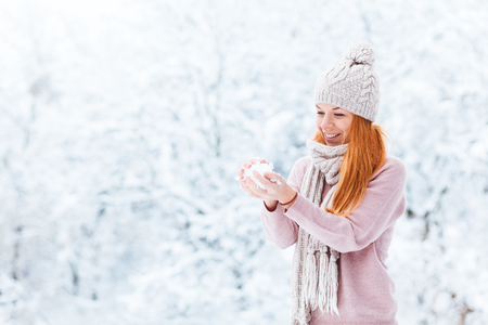 Young woman with snowball in the park Stock Photo