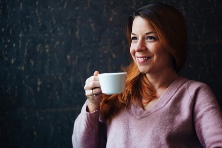 Portrait of a young woman enjoying drinking coffee