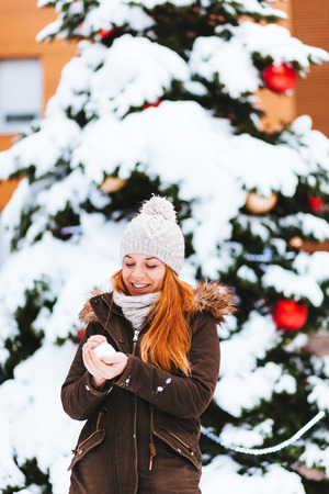 Young woman in front of the Christmas tree outdoors