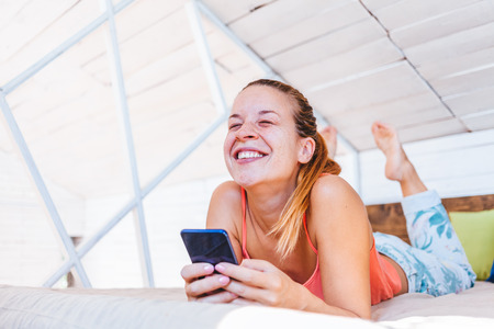 Young woman using cellphone at home, happy connection