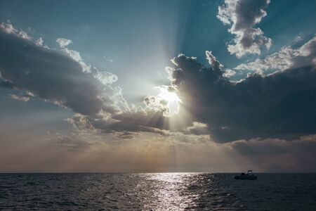 Sun breaking through the clouds on the sea