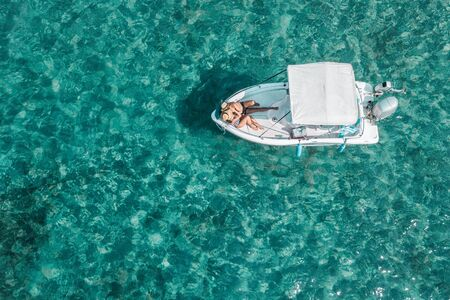 Vista aerea di una giovane coppia che si gode una giornata di sole in barca