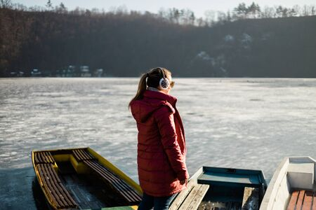 Young woman standing on the pier of a frozen lake in winter time