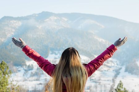 Woman standing with her hands raised facing the mountains in winter time 스톡 콘텐츠