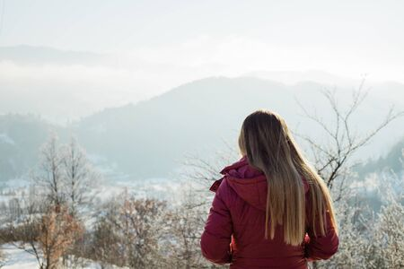 Young woman looking into the mountains in winter time 스톡 콘텐츠