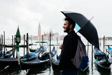 Young traveler in Venice, Italy standing by the canal on a rainy day