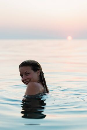 Young woman swimming in the sea in sunset