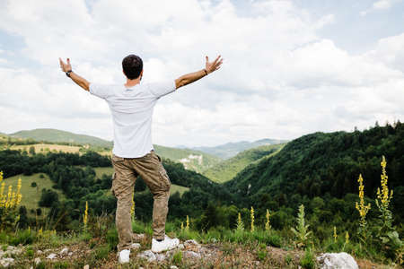 Young male nature explorer on top of mountain range
